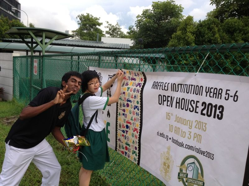 Ashlynna and Abilash putting up a banner outside the campus