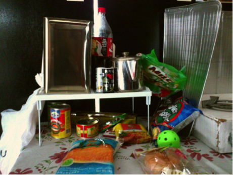 A table displaying an assortment of cheap but unhealthy foodstuffs, which can typically be found in a one-room flat.