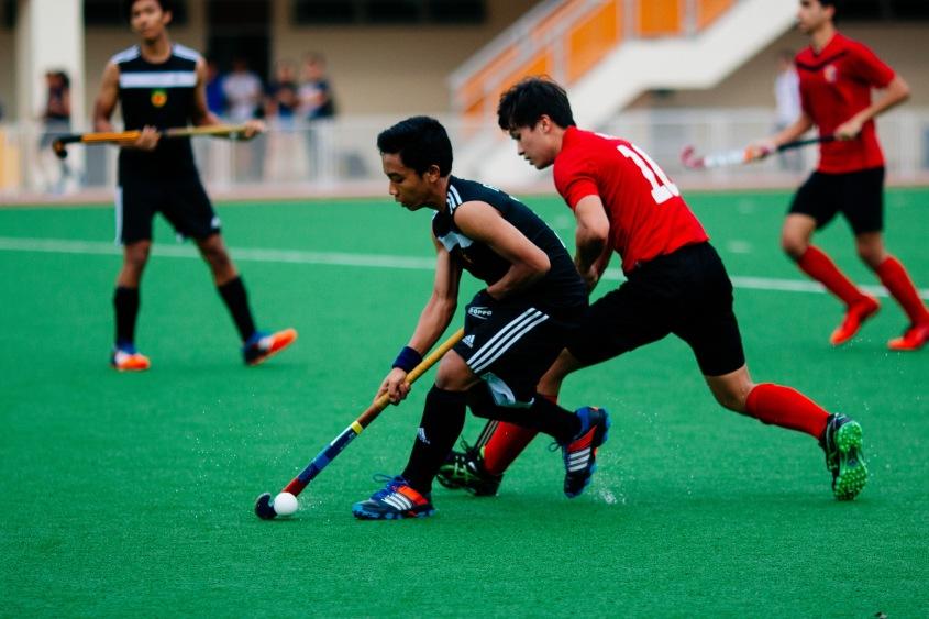 Adam Aniq (#16) keeping the ball away from an opponent.