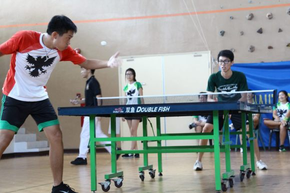 An MT player swings at a ball with his might, while a BB player is poised in a crouch, ready to react.