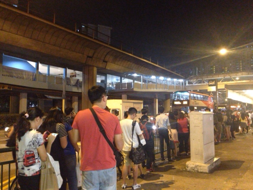 Commuters waiting orderly in line for the next bus as free feeder services were provided to send consumers home. (Source: CNA)